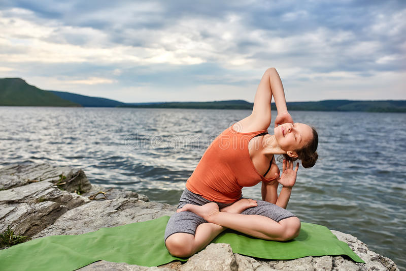 Gelukkige jonge vrouw die yogaoefening in openlucht op de steen doen dichtbij rivier stock foto's