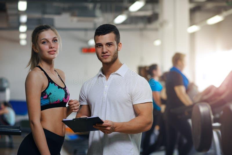 Gelukkige jonge vrouw en haar persoonlijke trainer in gymnastiek royalty-vrije stock foto