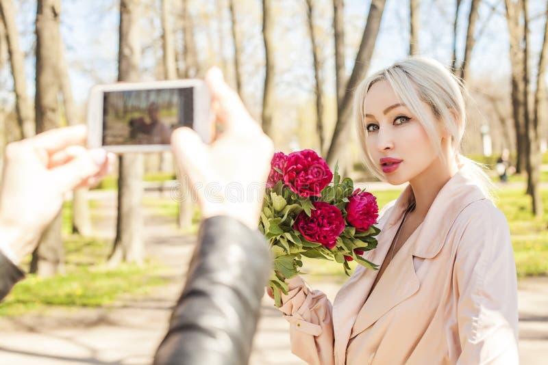 Gelukkige jonge vrouw en mannelijke hand met smartphone stock afbeelding