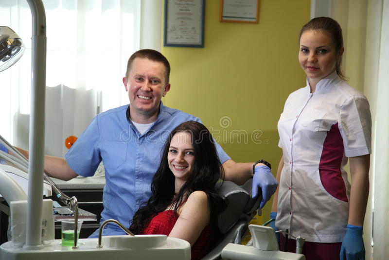 Gelukkige jonge vrouw en mannelijke tandarts na behandeling in kliniek stock foto's