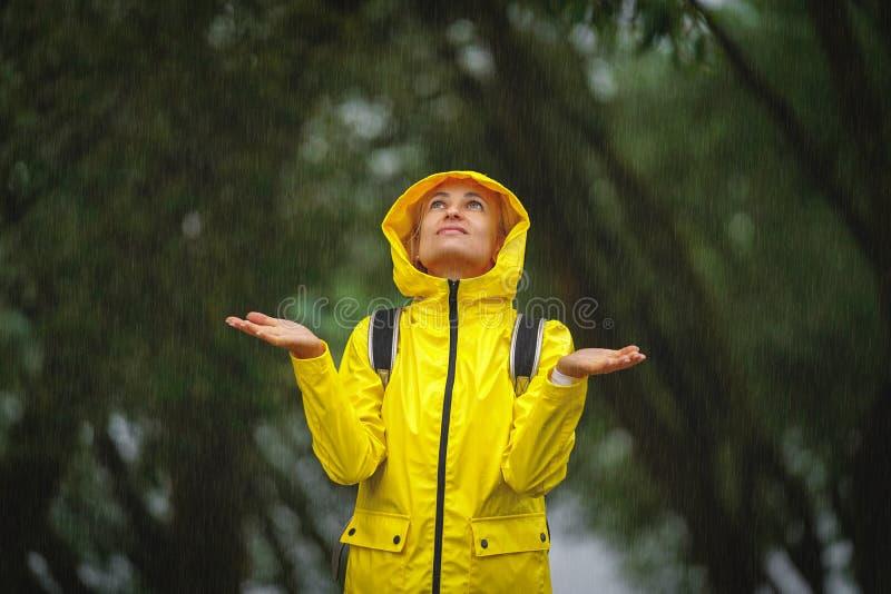 Gelukkige jonge vrouw in gele regenjas onder regen royalty-vrije stock afbeeldingen