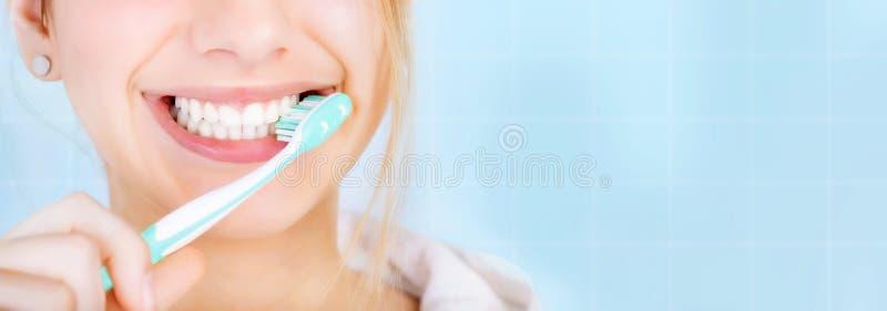 Gelukkige jonge vrouw het borstelen tanden stock afbeelding