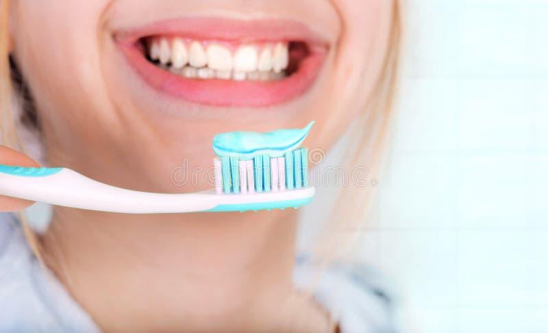 Gelukkige jonge vrouw het borstelen tanden royalty-vrije stock afbeeldingen
