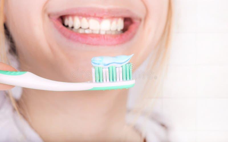 Gelukkige jonge vrouw het borstelen tanden stock afbeeldingen