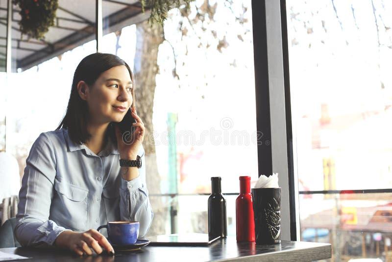 Gelukkige jonge vrouw het drinken cappuccino, latte, macchiato, thee, gebruikend tabletcomputer en sprekend op de telefoon in een stock fotografie