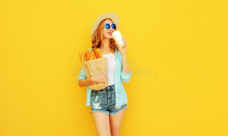 Gelukkige jonge vrouw het drinken het document van de koffieholding zak die met lange witte broodbaguette strohoed, borrels op kl stock fotografie