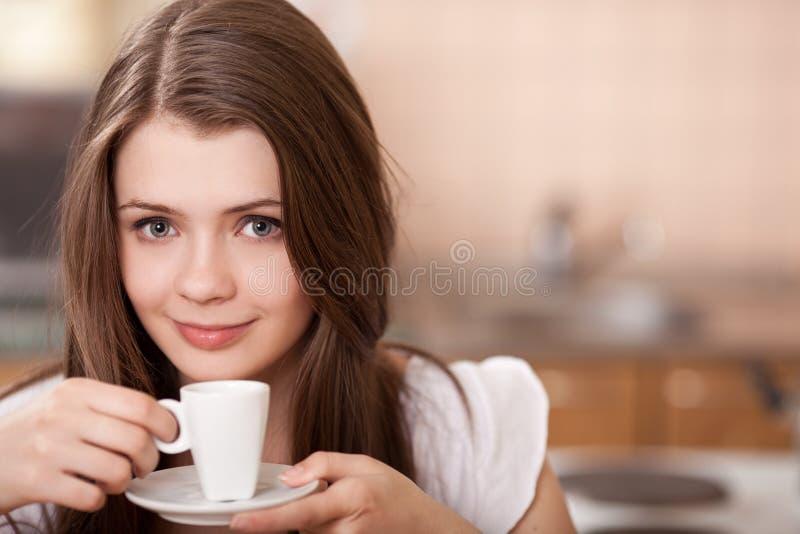 Gelukkige jonge vrouw het drinken koffie thuis stock fotografie