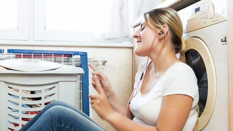 Gelukkige jonge vrouw het luisteren muziek met oortelefoons terwijl het doen van huishoudelijk werk bij wasserijruimte royalty-vrije stock foto