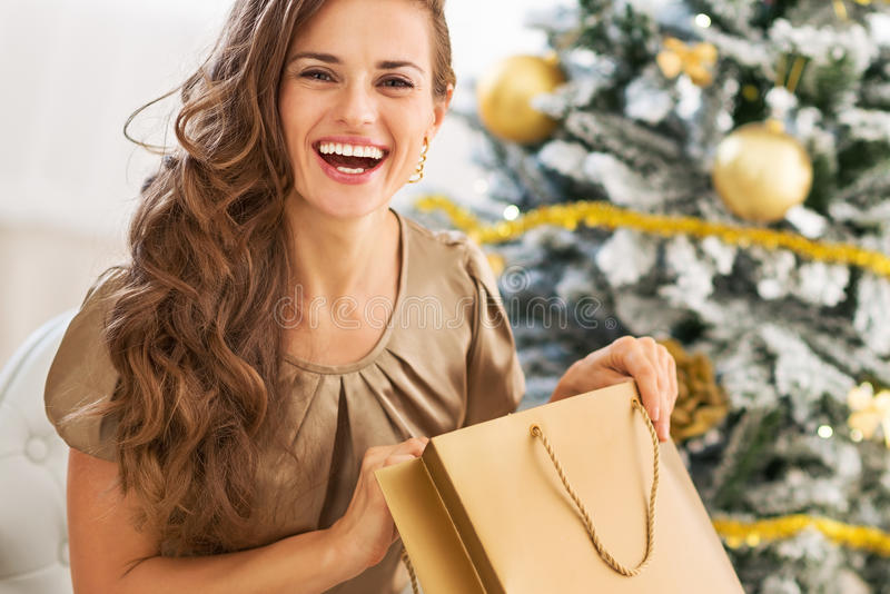 Gelukkige jonge vrouw het openen het winkelen zak dichtbij Kerstmisboom stock fotografie