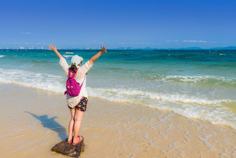 Gelukkige jonge vrouw het uitspreiden hand op het strand voor ontspannen stock foto's