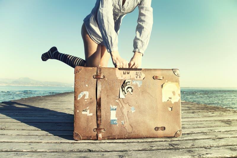 Gelukkige jonge vrouw klaar om met haar koffer te reizen stock afbeeldingen