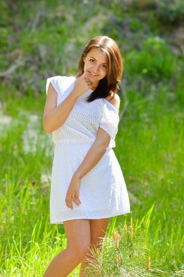 Gelukkige jonge vrouw in korte witte de zomerkleding op groen gras royalty-vrije stock foto