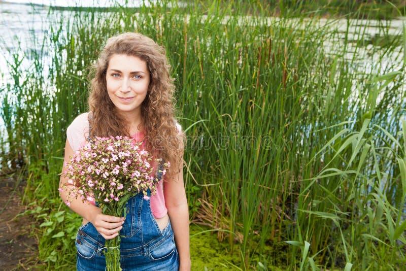 Gelukkige jonge vrouw met boeket van roze bloemen als gift in de zomer stock fotografie