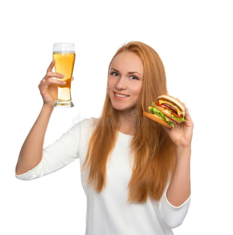 Gelukkige jonge vrouw met de mok van het lagerbierbier en hamburgersandwich hambur royalty-vrije stock foto's