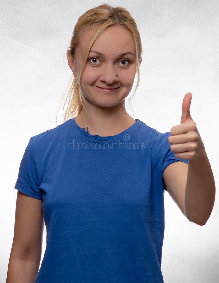 Gelukkige jonge vrouw met duimen omhoog in toevallig blauw overhemd stock foto's