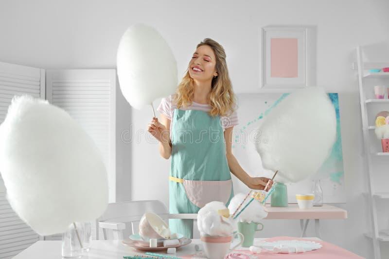 Gelukkige jonge vrouw met gesponnen suiker en snoepjes op lijst royalty-vrije stock foto's