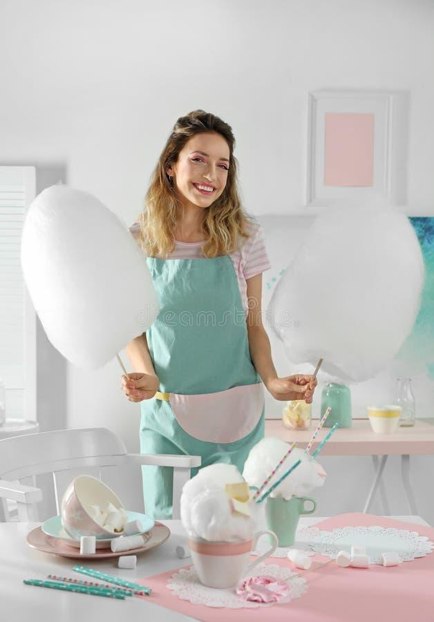 Gelukkige jonge vrouw met gesponnen suiker en snoepjes op lijst stock foto