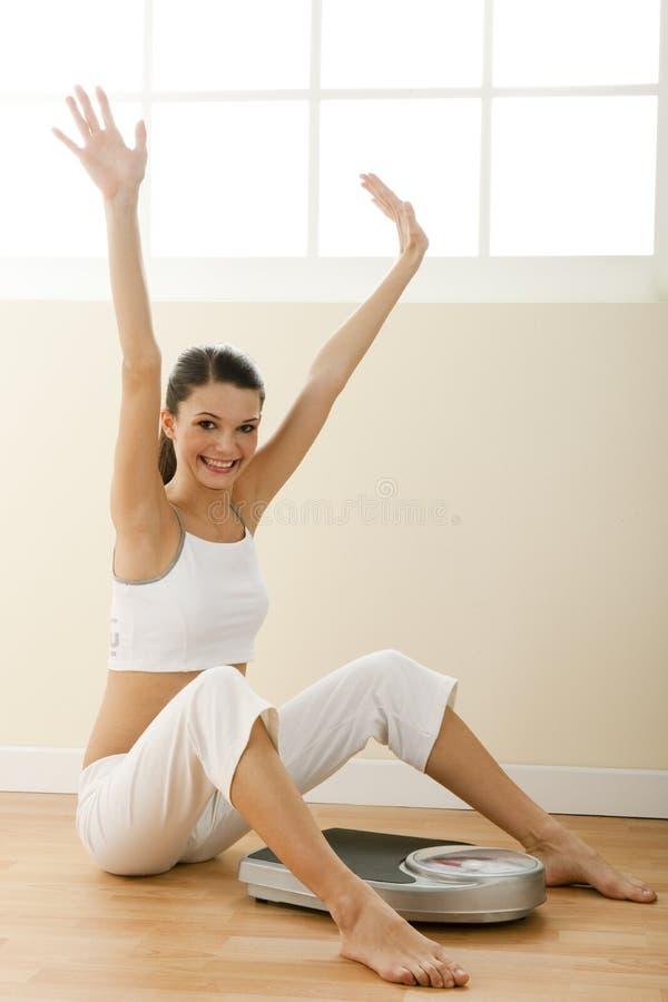 Gelukkige jonge vrouw met gewichtsschaal stock fotografie