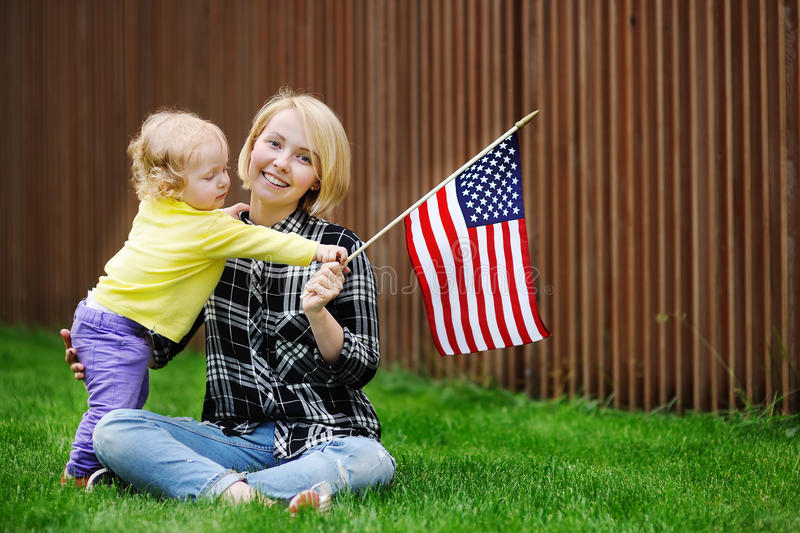 Gelukkige jonge vrouw met haar peutermeisje die Amerikaanse vlag houden royalty-vrije stock foto