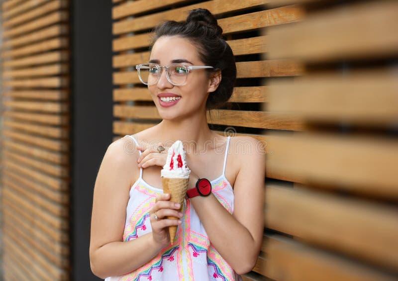 Gelukkige jonge vrouw met heerlijk roomijs in wafelkegel stock afbeelding