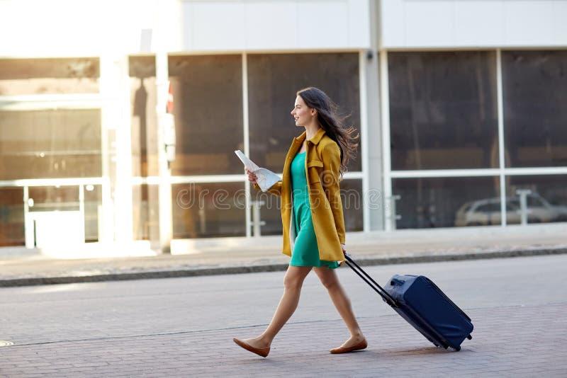 Gelukkige jonge vrouw met reiszak en kaart in stad royalty-vrije stock foto's