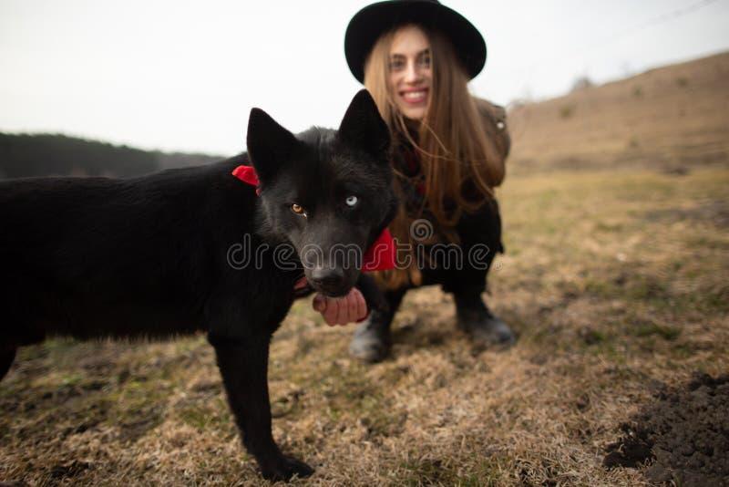 Gelukkige jonge vrouw met zwarte hoed, die met haar zwarte hond op de kust van het meer plaing royalty-vrije stock fotografie