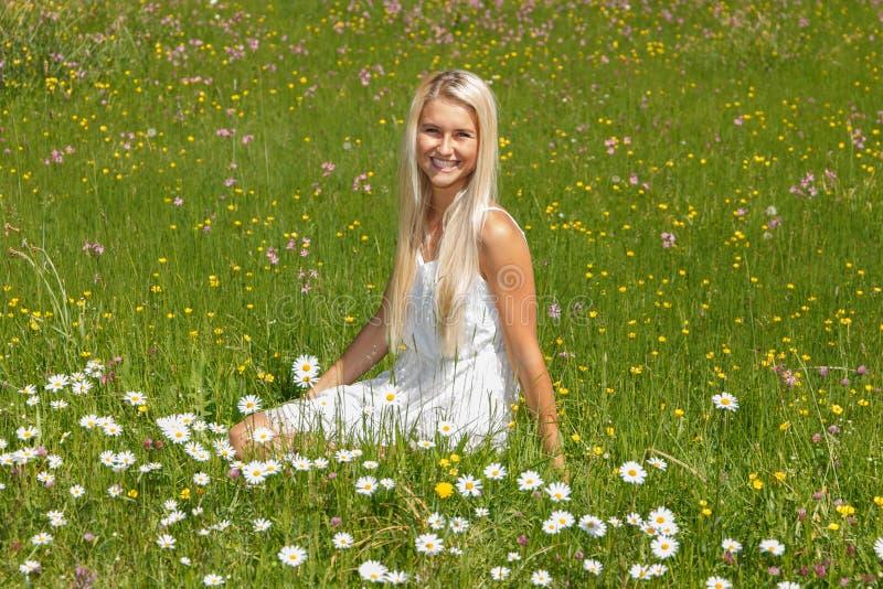 Gelukkige jonge vrouw op een bloemweide stock afbeelding