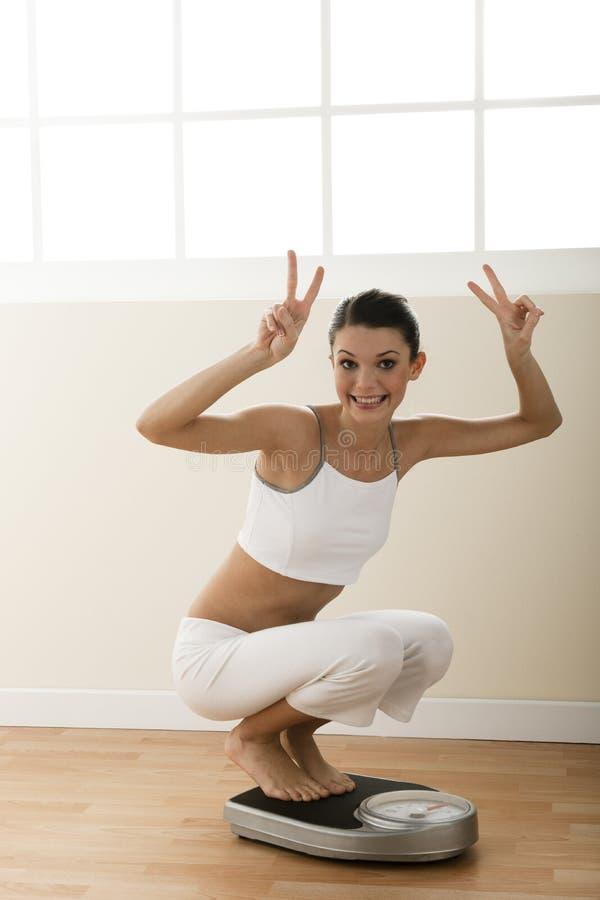 Gelukkige jonge vrouw op gewichtsschaal royalty-vrije stock foto