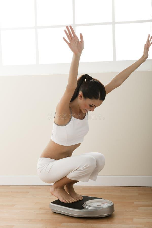 Gelukkige jonge vrouw op gewichtsschaal royalty-vrije stock afbeelding