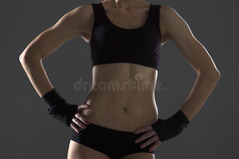 Gelukkige jonge vrouw in sporten die het glimlachen kleden Spiergeschiktheidsmodel op zwarte achtergrond die weg exemplaarruimte  royalty-vrije stock foto's