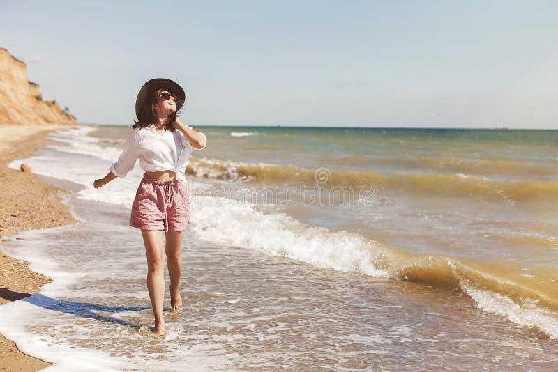 Gelukkige jonge vrouw in wit overhemd en hoed die en pret met golven op zonnig strand in werking stellen hebben En Hipster slank  royalty-vrije stock afbeelding