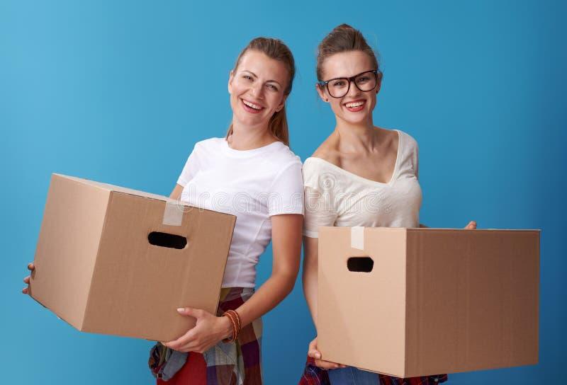 Gelukkige jonge vrouwelijke kamergenoten die kartondozen op blauw houden stock afbeeldingen