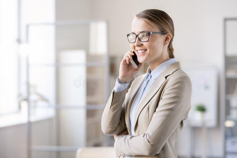 Gelukkige jonge vrouwelijke manager die aan klant op telefoon spreken stock fotografie