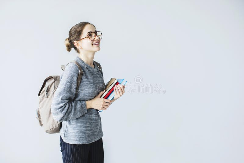 Gelukkige jonge vrouwelijke student die upwards dragende boeken van de rugzakholding kijken stock foto