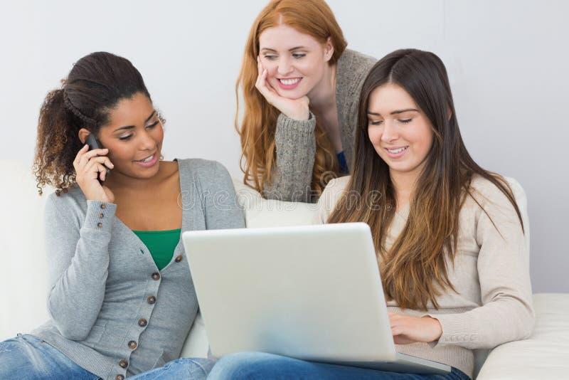 Gelukkige jonge vrouwelijke vrienden die laptop en cellphone gebruiken stock foto