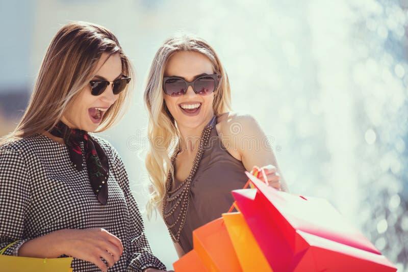 Gelukkige jonge vrouwen die het winkelen zakken onderzoeken royalty-vrije stock foto