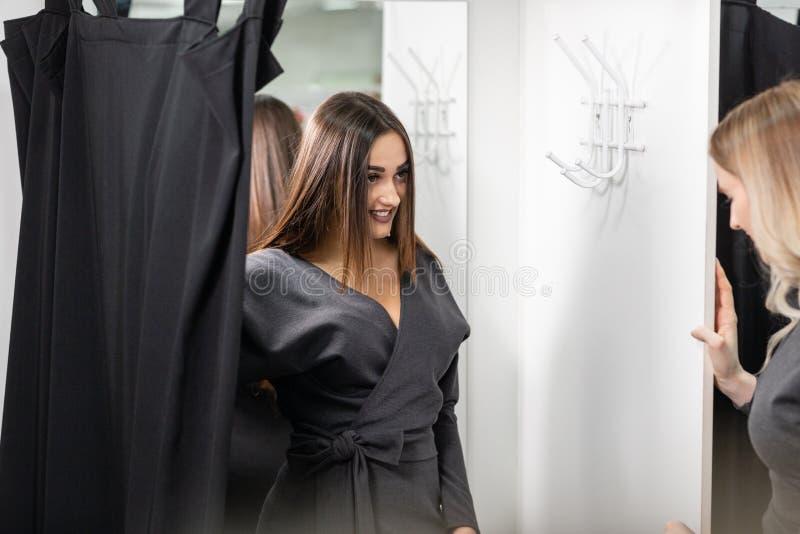 Gelukkige jonge vrouwen die kleren in wandelgalerij kiezen of opslag kleden Verkoop, manier, consumentismeconcept stock foto's