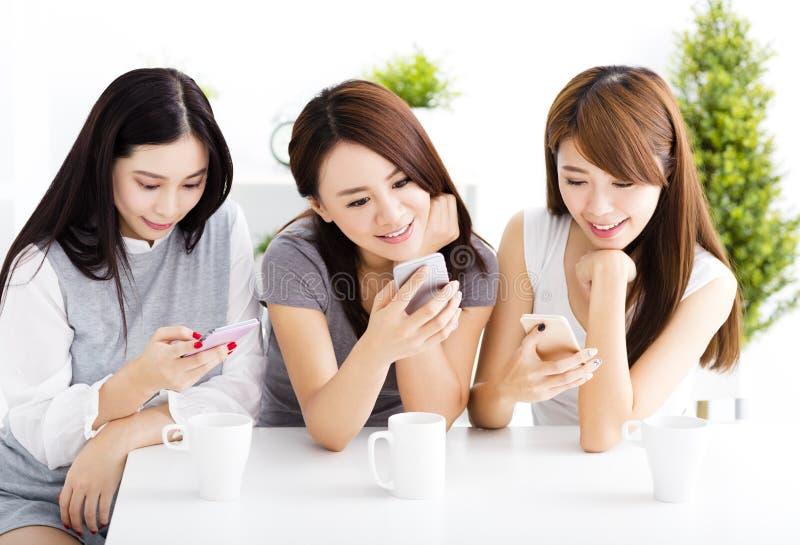 Gelukkige jonge vrouwen die op slimme telefoon in woonkamer letten royalty-vrije stock foto