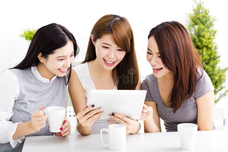 gelukkige jonge vrouwen die op tablet in woonkamer letten royalty-vrije stock afbeelding