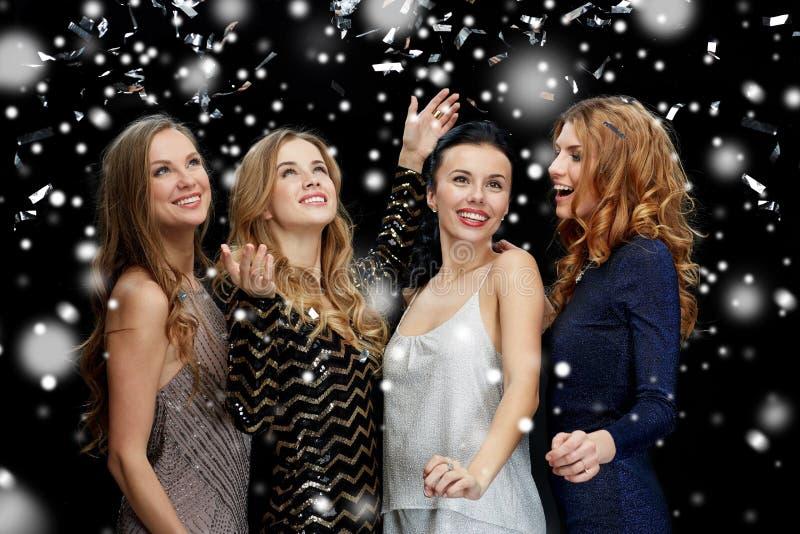 Gelukkige jonge vrouwen die over sneeuw dansen stock afbeelding