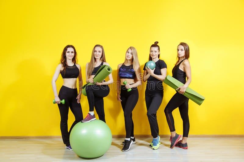 Gelukkige jonge vrouwen die zich en na het uitoefenen glimlachen verenigen Groep vrouwelijke vrienden die na training ontspannen royalty-vrije stock foto