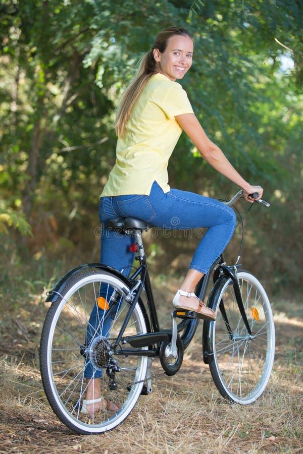 Gelukkige jonge vrouwen duwende fiets op bos stock foto's