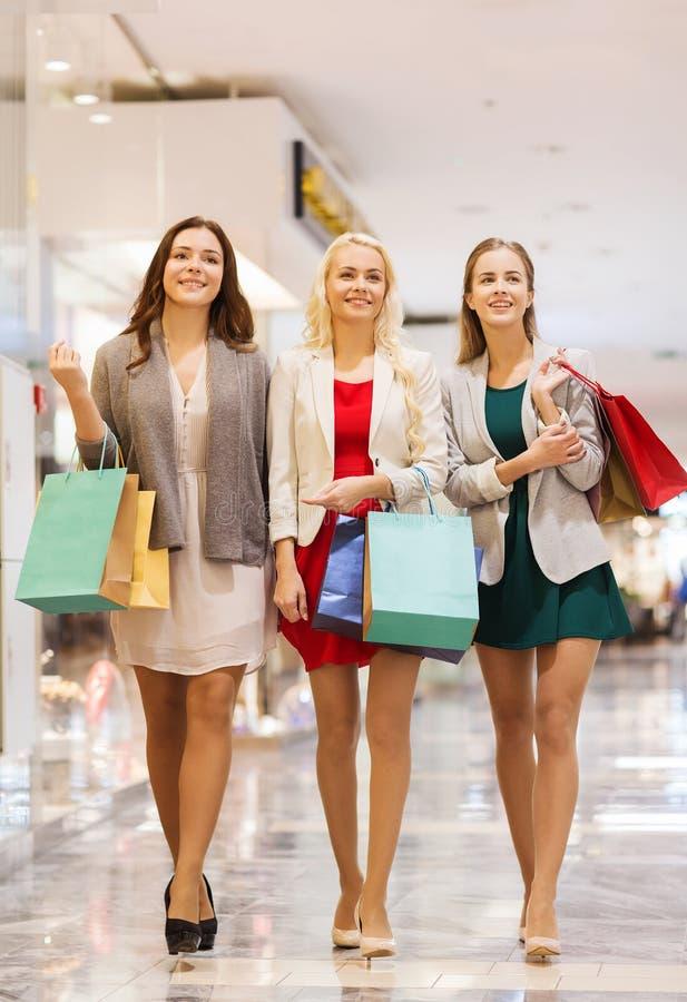 Gelukkige jonge vrouwen met het winkelen zakken in wandelgalerij royalty-vrije stock fotografie