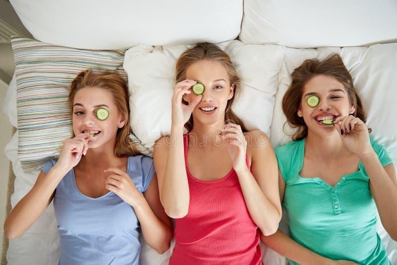 Gelukkige jonge vrouwen met komkommermasker die in bed liggen stock foto's