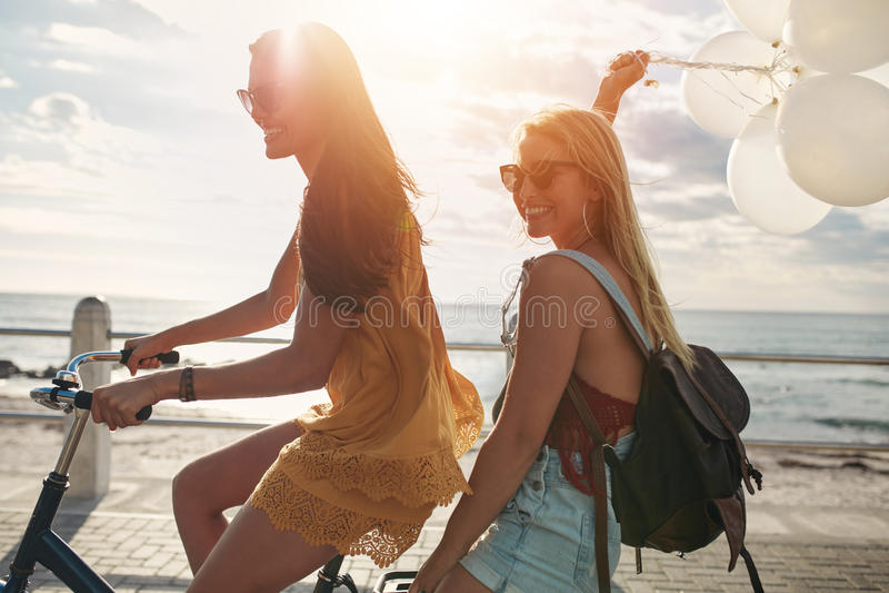 Gelukkige jonge vrouwen op fiets samen met ballons stock foto