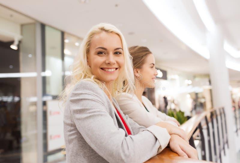 Gelukkige jonge vrouwen in wandelgalerij of commercieel centrum royalty-vrije stock afbeeldingen