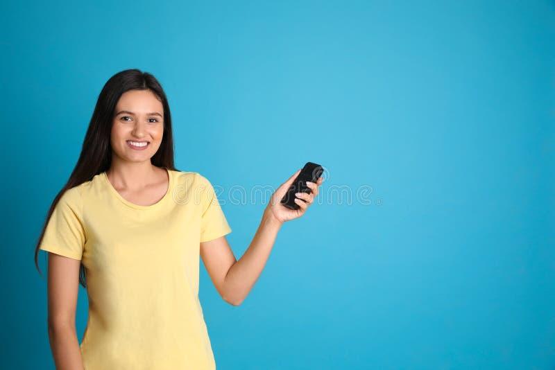 Gelukkige jonge vrouwen werkende airconditioner met afstandsbediening op lichtblauwe achtergrond Ruimte voor stock foto