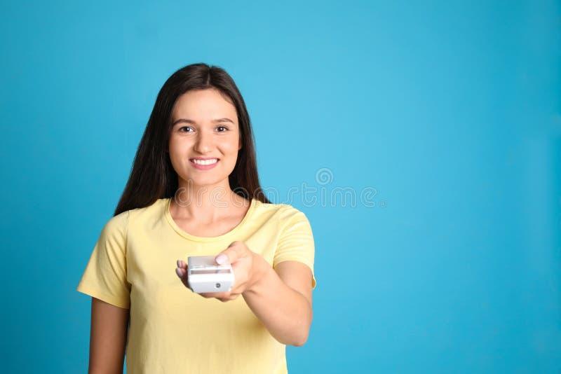 Gelukkige jonge vrouwen werkende airconditioner met afstandsbediening op lichtblauwe achtergrond Ruimte voor stock fotografie