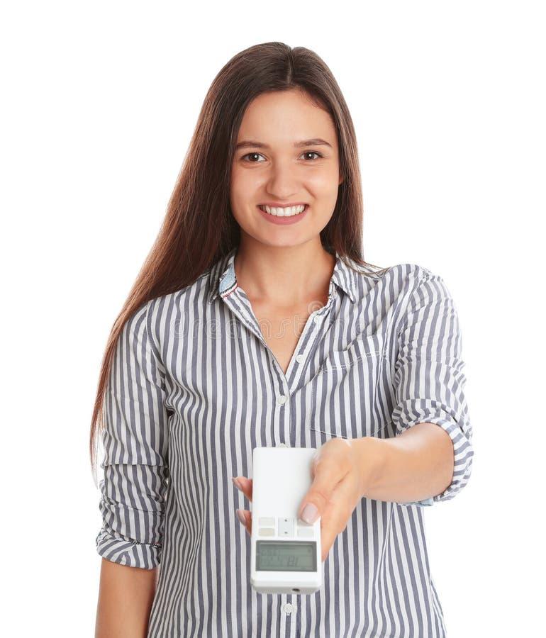 Gelukkige jonge vrouwen werkende airconditioner met afstandsbediening op wit royalty-vrije stock foto