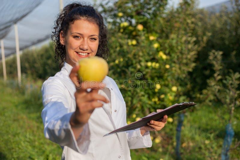 Gelukkige jonge vrouwenagronoom met groene appel in haar hand stock foto